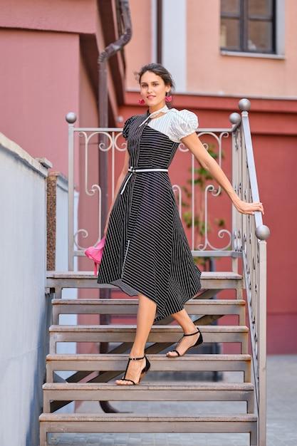 Signora carina e alla moda in abito lungo a strisce che scende le scale Foto Premium