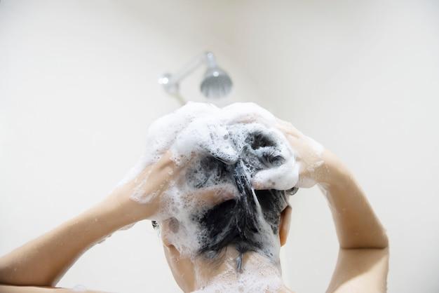 Signora che usa shampoo lavarsi / pulirsi i capelli in un bagno con spruzzi d'acqua Foto Gratuite