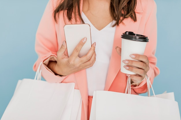 Signora con caffè e smartphone su fondo blu Foto Gratuite