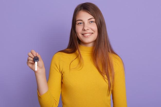 Signora con il sorriso affascinante che sta contro la parete lilla, tenente chiave dell'automobile Foto Gratuite