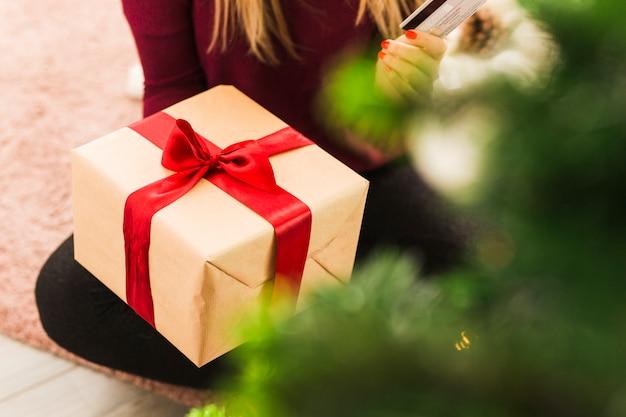Signora con scatola regalo e carta di plastica sul tappeto Foto Gratuite