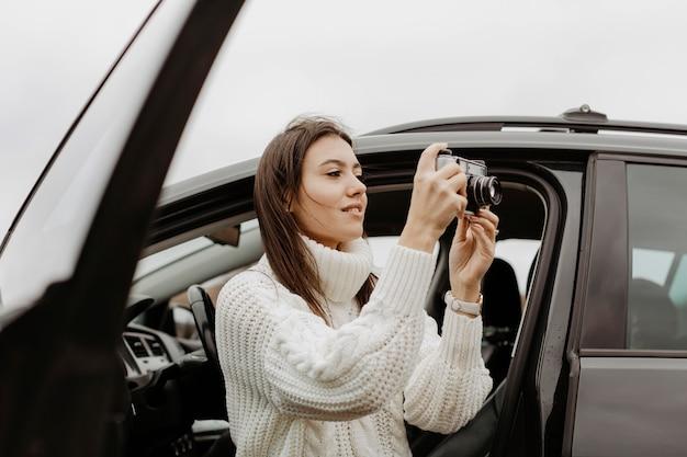 Signora di vista laterale che prende una foto Foto Gratuite