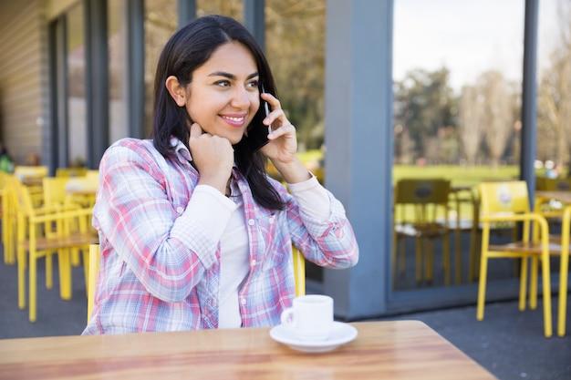 Signora felice che comunica sul telefono e che beve caffè in caffè della via Foto Gratuite