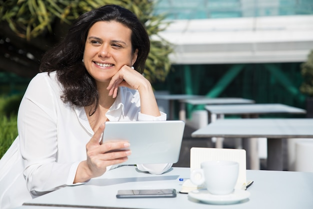 Signora graziosa sorridente che lavora e che utilizza compressa nel caffè della via Foto Gratuite