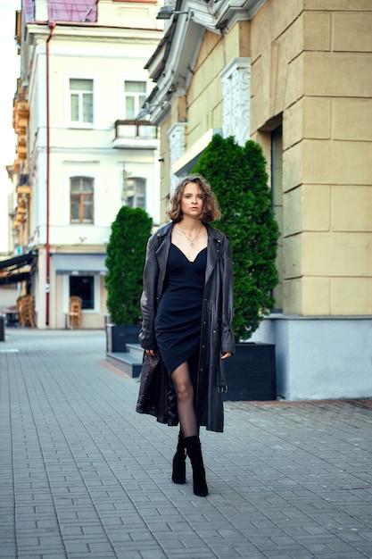Signora in abito da sera e mantello di cuoio da uomo spalancato che cammina per strada Foto Premium