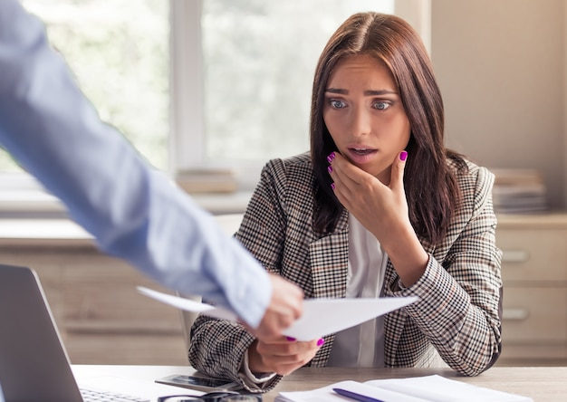 Signora in eleganti abiti formali è scioccata nel prendere un documento. Foto Premium