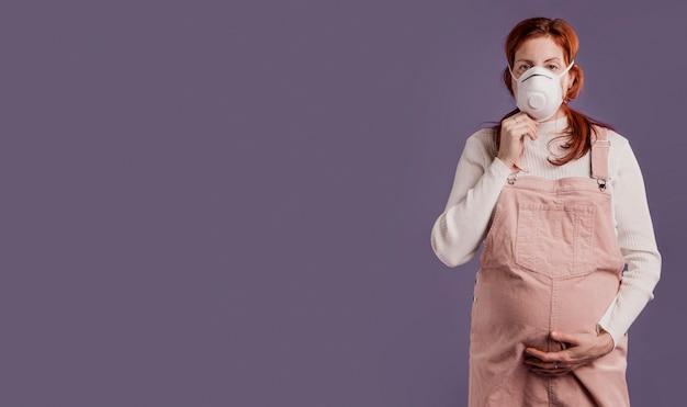 Signora incinta che indossa una maschera protettiva Foto Gratuite