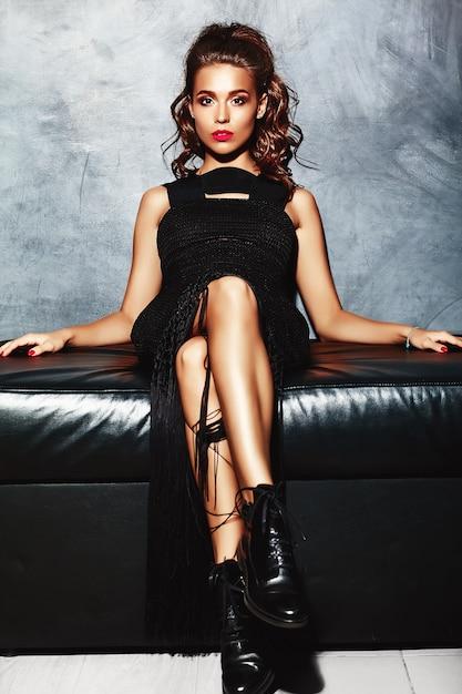 Signora modello bella donna sexy con labbra rosse in abito elegante nero seduto sul divano vicino alla parete grigia Foto Gratuite