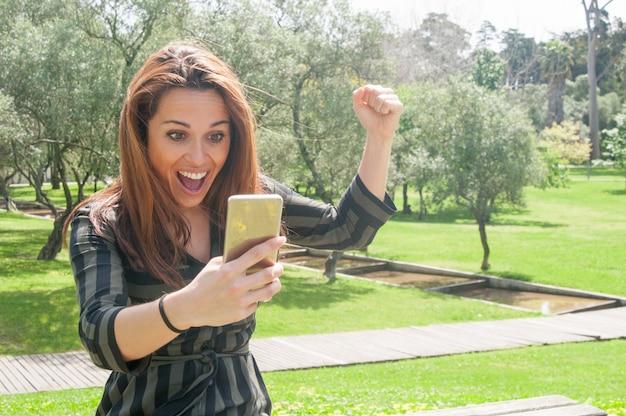 Signora overjoyed con il telefono cellulare che celebra la vittoria Foto Gratuite