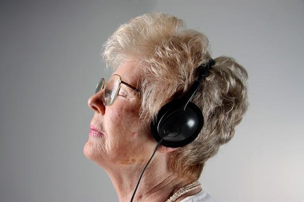 Signora senior sul profilo con le cuffie Foto Premium