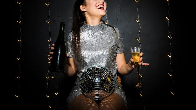 Signora sorridente con palla da discoteca, bottiglia e bicchiere Foto Gratuite