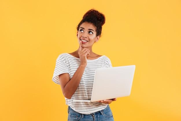 Signora sorridente premurosa che osserva in su e che giudica computer portatile isolato Foto Gratuite
