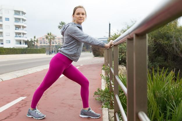 Signora sportiva in forma in leggings rosa facendo esercizio con ringhiera Foto Gratuite