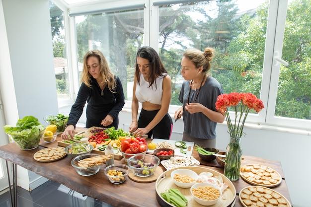 Signore seri che cucinano e tagliano le verdure in cucina Foto Gratuite