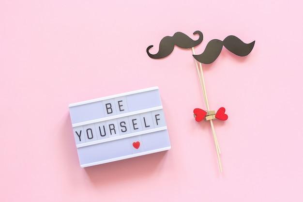 Sii te stesso testo lightbox, coppia puntelli di carta baffi su sfondo rosa. omosessualità amore gay Foto Premium