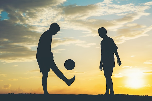 Silhouette di bambini giocano a calcio di calcio Foto Gratuite