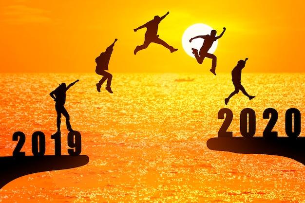 Silhouette di giovani uomini d'affari che saltano dal 2019 al 2020 Foto Premium