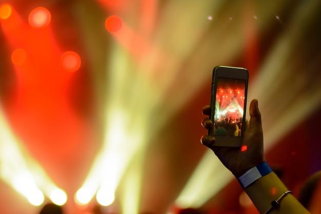 Silhouette di mani con uno smartphone sullo sfondo degli artisti cantanti alla luce delle luci rosse Foto Premium