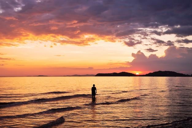 Silhouette di persone che giocano in mare con il cielo al tramonto drammatico Foto Premium