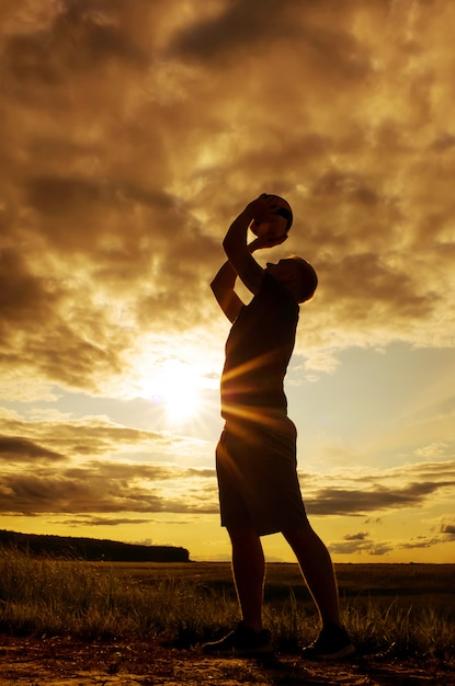 Silhouette di un uomo con una palla. Foto Premium