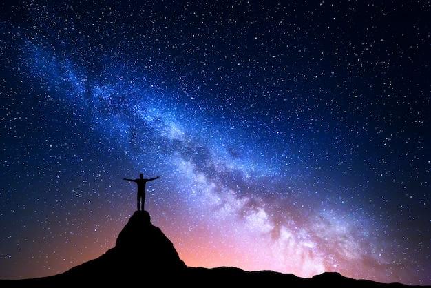 Silhouette di un uomo in piedi sul picco di montagna Foto Premium