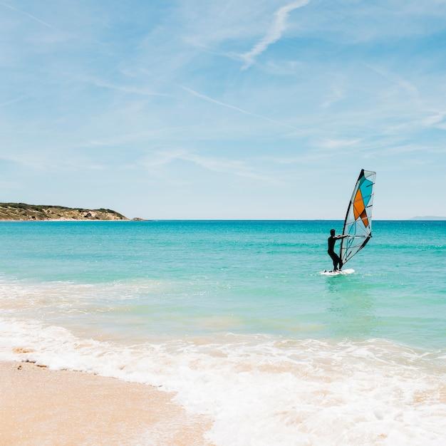 Silhouette di un windsurfer sul mare blu. Foto Gratuite