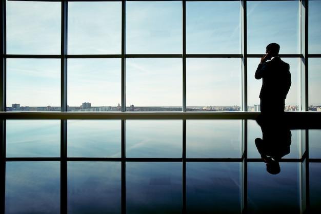 Silhouette di uomo d'affari godendo della vista Foto Gratuite