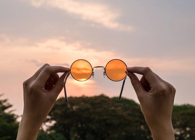 Silhouette, sfocata, arte tono di occhiali da sole arancione con sfondo del cielo di sera Foto Premium