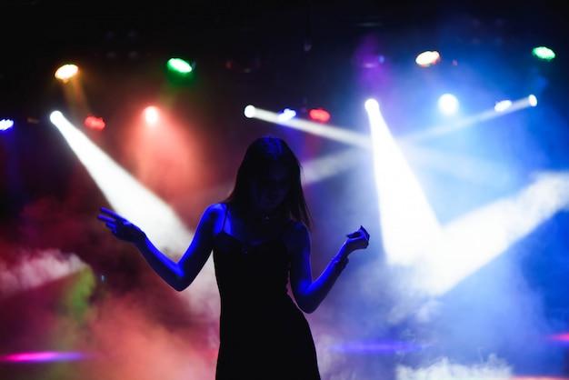 Siluetta ballante della ragazza in un night-club Foto Premium