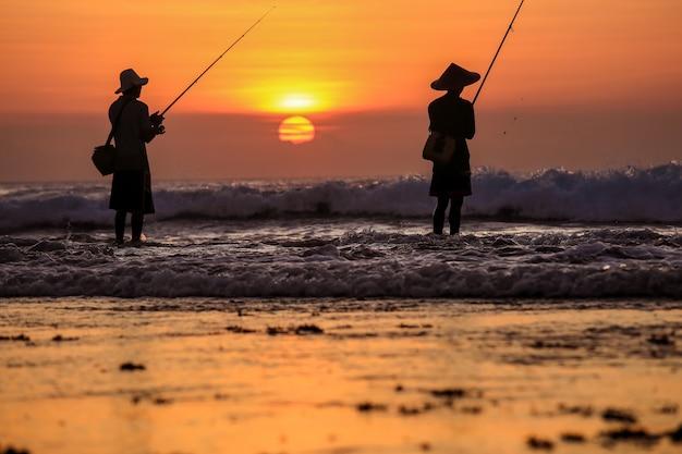 Siluetta dei pescatori sull'oceano calmo con i raggi del tramonto alla spiaggia di jimbaran, bali, indonesia Foto Premium