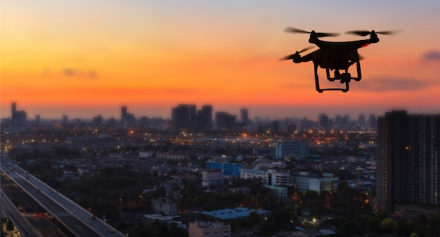 Siluetta del drone che vola sopra la città al tramonto Foto Premium