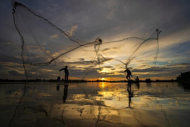 Siluetta del pescatore sul peschereccio con rete sul lago al tramonto, tailandia Foto Premium