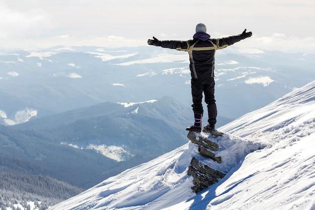 Siluetta del turista solo che sta sulla cima della montagna nevosa nella posa del vincitore con le mani sollevate che godono della vista e del risultato il giorno di inverno soleggiato luminoso. avventura, attività all'aria aperta, stile di vita sano. Foto Premium