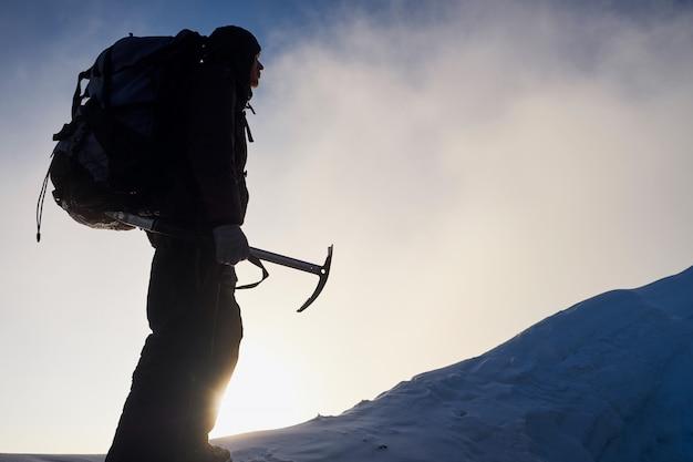 Siluetta dell'uomo alpinista che va alla cima della montagna all'alba. con in mano uno strumento per il ghiaccio Foto Premium