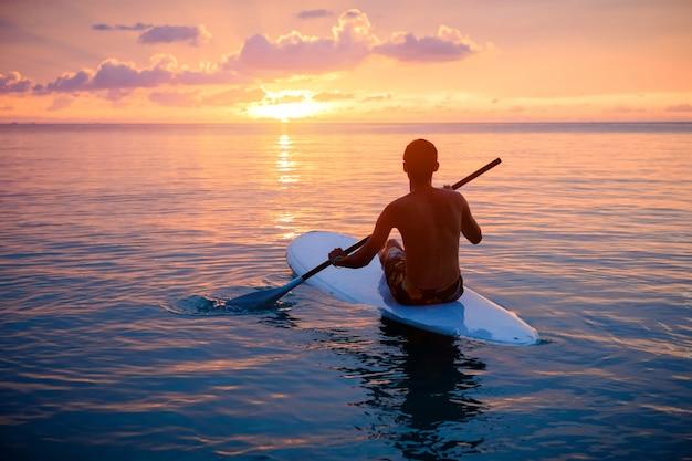 Siluetta dell'uomo che paddleboarding al tramonto Foto Premium