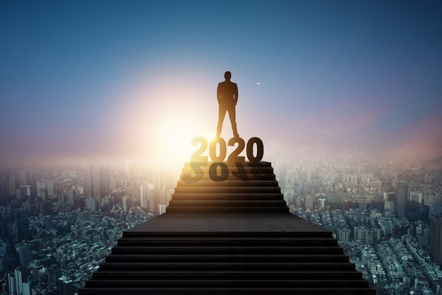 Siluetta dell'uomo d'affari che sta sulla scala e sul 2020 Foto Premium