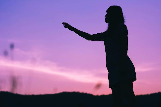 Siluetta della donna di tristezza che sta contro il fondo di tramonto Foto Premium