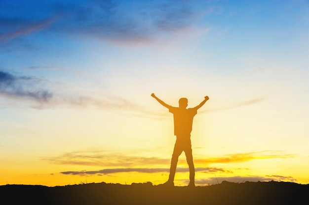 Siluetta della felicità di successo di celebrazione dell'uomo su una cima della montagna fondo di tramonto del cielo di sera. Foto Premium