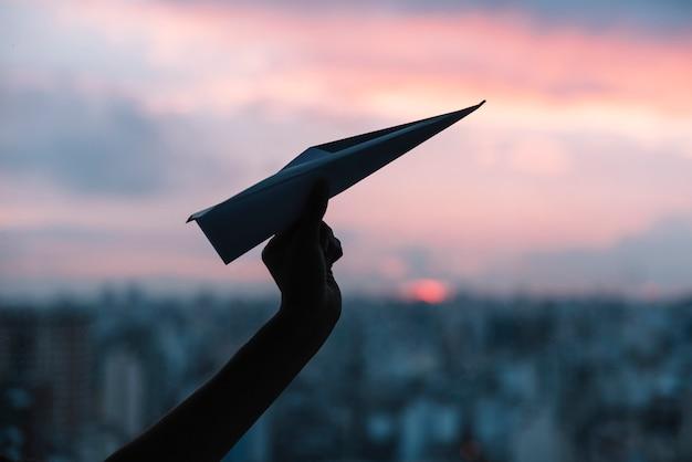 Siluetta della mano di una persona che tiene aeroplano di carta contro il cielo drammatico Foto Gratuite