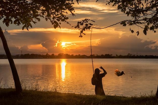 Siluetta della pesca del pescatore dal lato del fiume nel tramonto Foto Premium