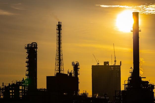 Siluetta della pianta di industria della raffineria di petrolio e gas con illuminazione di scintillio e alba di mattina Foto Premium