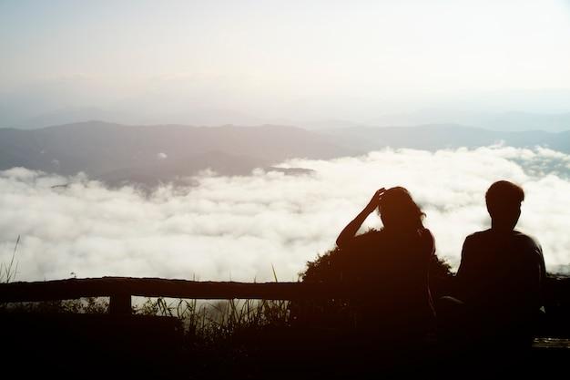 Siluetta delle coppie su una valle dell'alta montagna con alba di mattina. Foto Premium