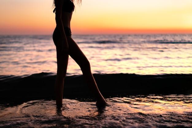 Siluetta di bella giovane donna pensierosa gracile con una sensazione di libertà ad un bel tramonto Foto Premium