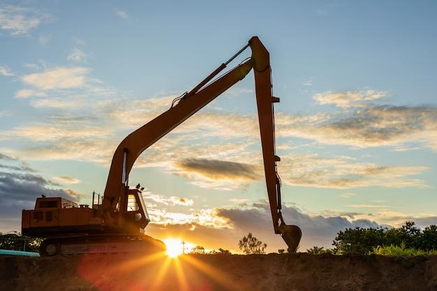 Siluetta di grande escavatore che scava il terreno sul sito Foto Premium