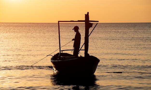 Siluetta di tempo di tramonto del pescatore e della barca. Foto Premium