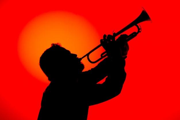 Siluetta di un musicista jazz che suona la tromba, isolata nel fondo rosso. concetto di musica jazz. Foto Premium