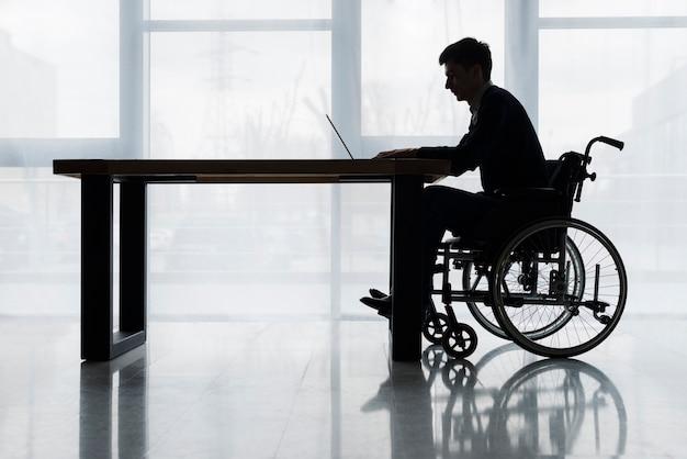 Siluetta di un uomo d'affari che si siede sulla sedia a rotelle facendo uso del computer portatile sul tavolo davanti alla finestra Foto Gratuite