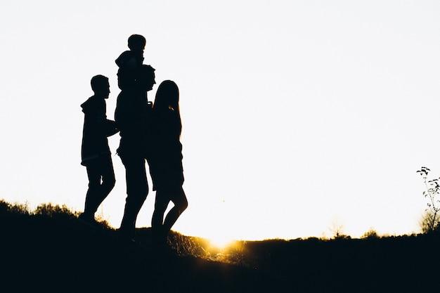 Siluetta di una famiglia che cammina entro l'ora del tramonto Foto Gratuite