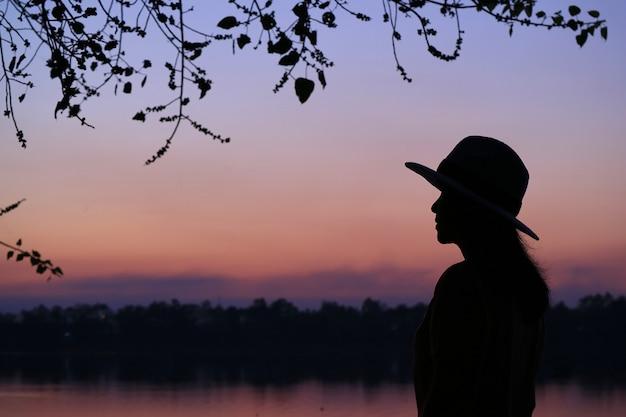 Siluetta di una giovane donna contro bello colore viola del cielo di sera Foto Premium