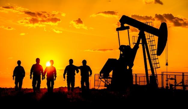 Siluetta di una pompa di petrolio greggio del lavoratore del giacimento di petrolio al tramonto. Foto Premium